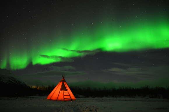 Illuminated tepee under the Northern Lights in Abisko