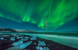 Aurora over black volcanic beaches in Iceland as seen on superjeep Aurora Hunt