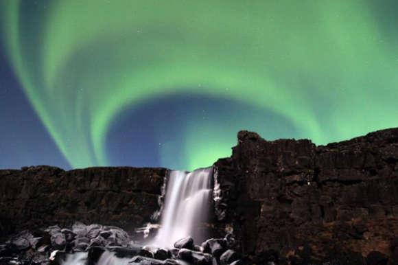 Skogafoss waterfall beneath the Northern Lights
