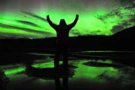 Man celebrating Northern Lights in Sweden