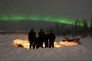 Sami New Year at Máttaráhkká Northern lights Lodge with outside fire and auroras overhead